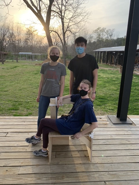 one student sits in a handmade chair while two students stand behind