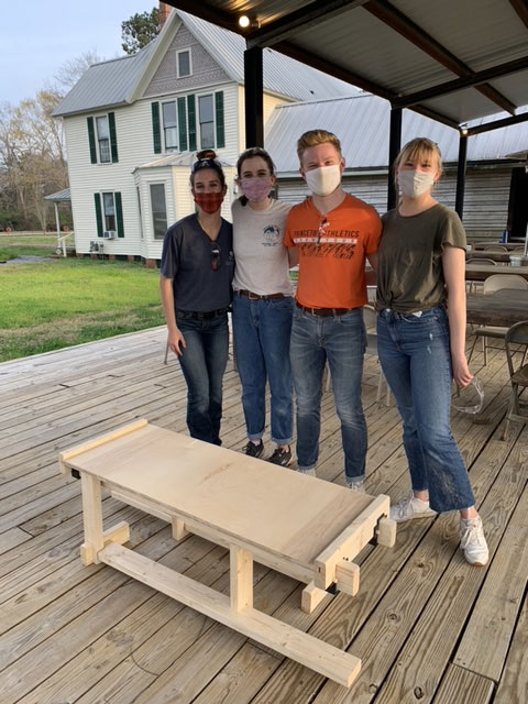 four students stand together behind a hand-built bench