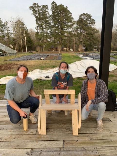 three students kneel behind their handmade chair
