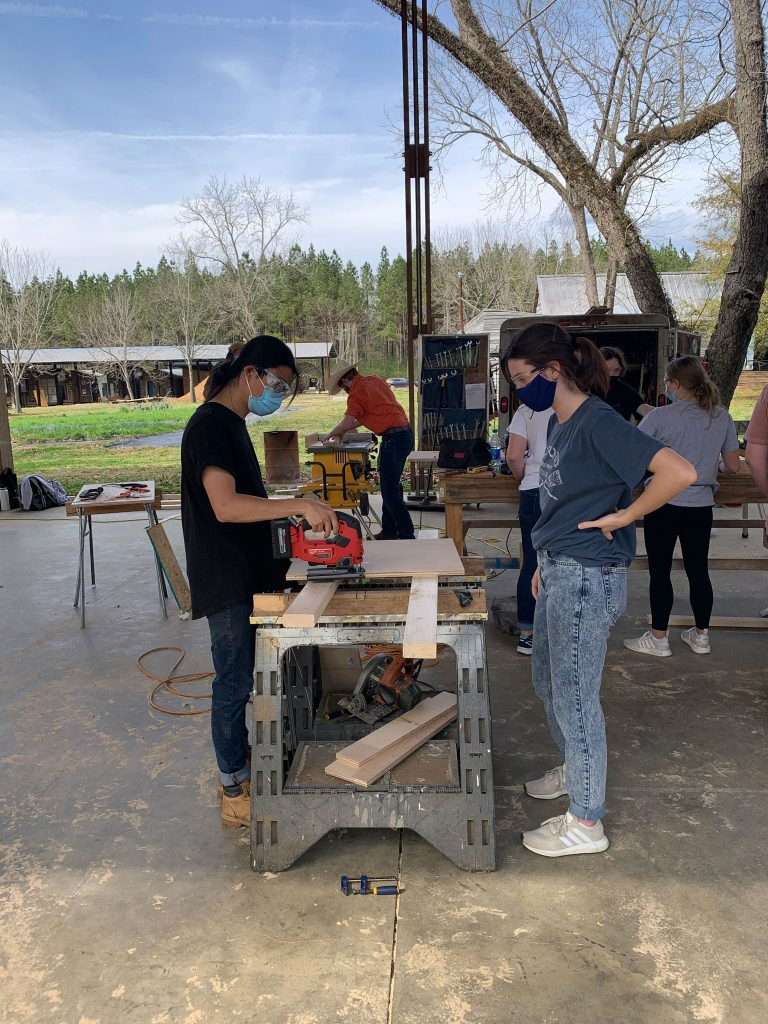 a graduate student shows a 1st-year student how to use a jig saw