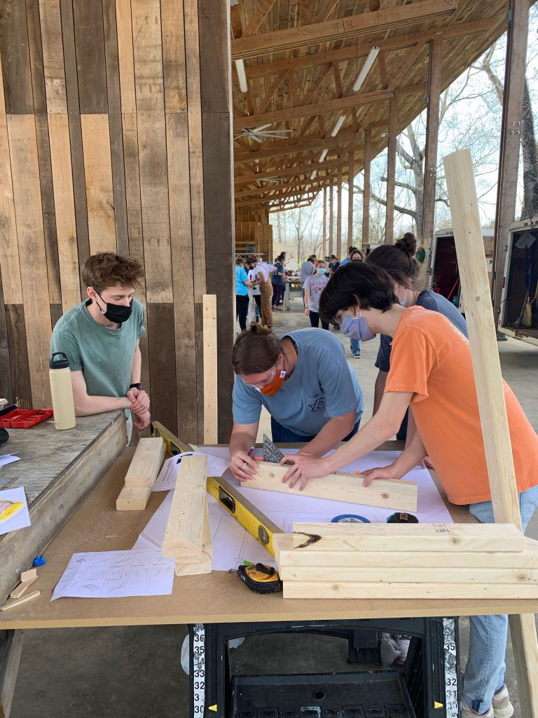 students work together to scribe a line onto a 2x4