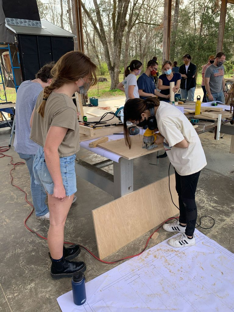 a graduate student watches on as a 1st-year student uses a jig saw