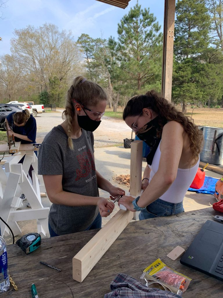 students clamp a small plastic joint to two 2x4 pieces of wood