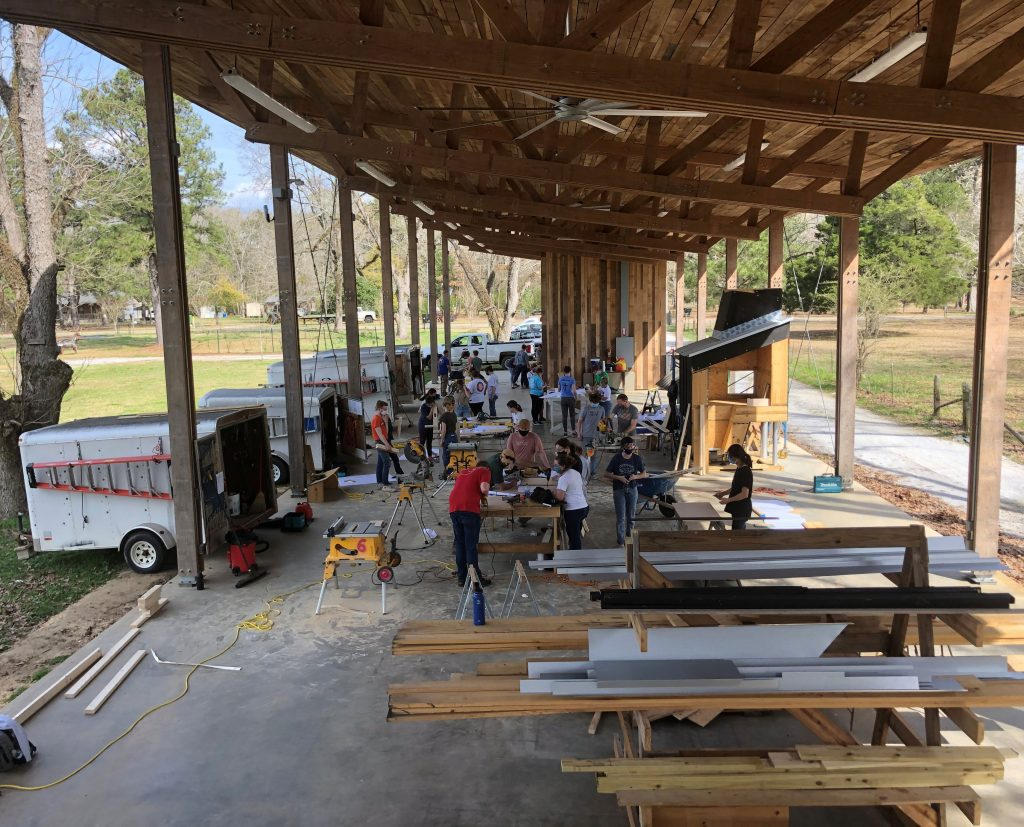 an aerial view of students and faculty using power tools together under a large wooden pavilion
