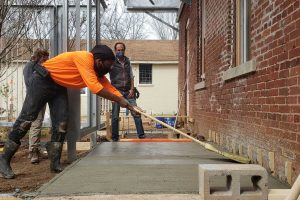Student using boom to finish concrete