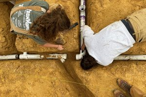 Two student from above gluing pipes in the dirt