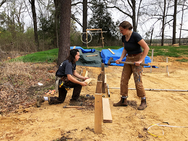 Two students with a sledge hammer and batter boards