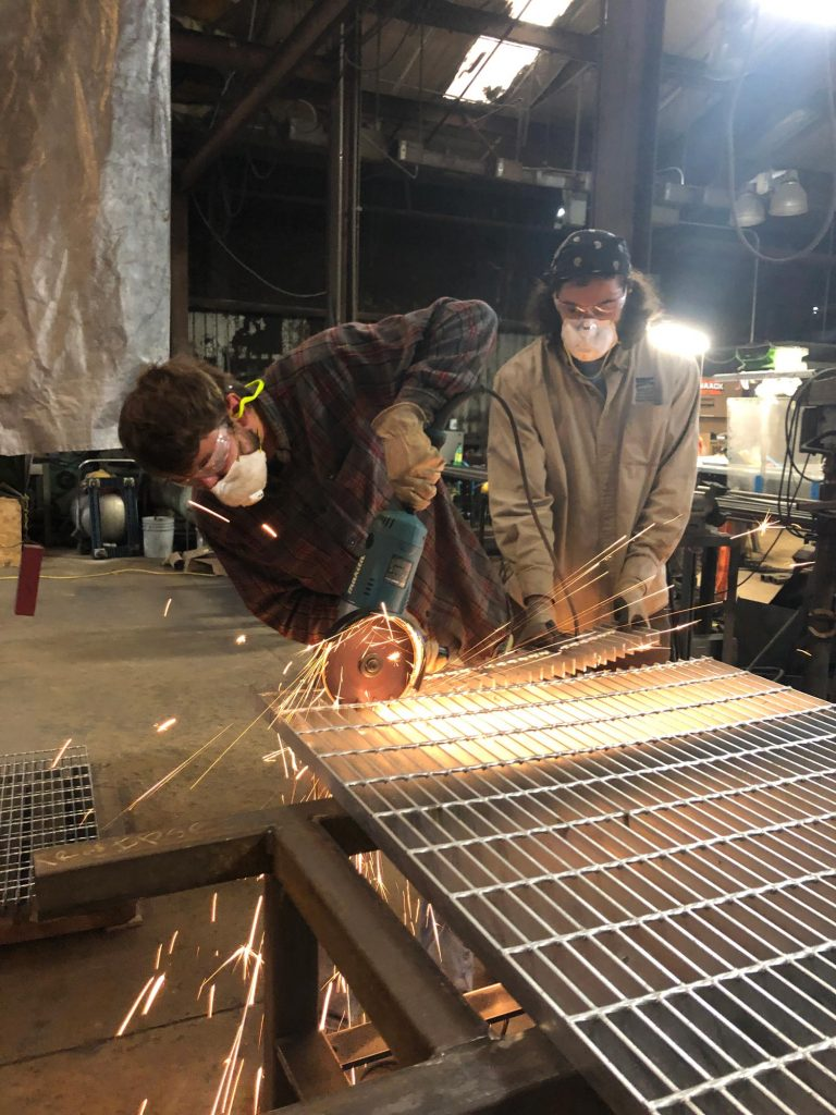 Cory and Rowe cutting metal grate with large angle grinder