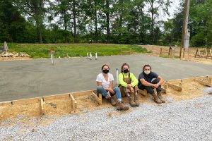 three team members sitting in front of a new slab
