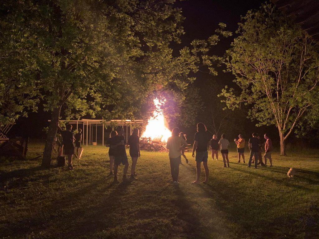 a group of people stand in front of a large bonfire