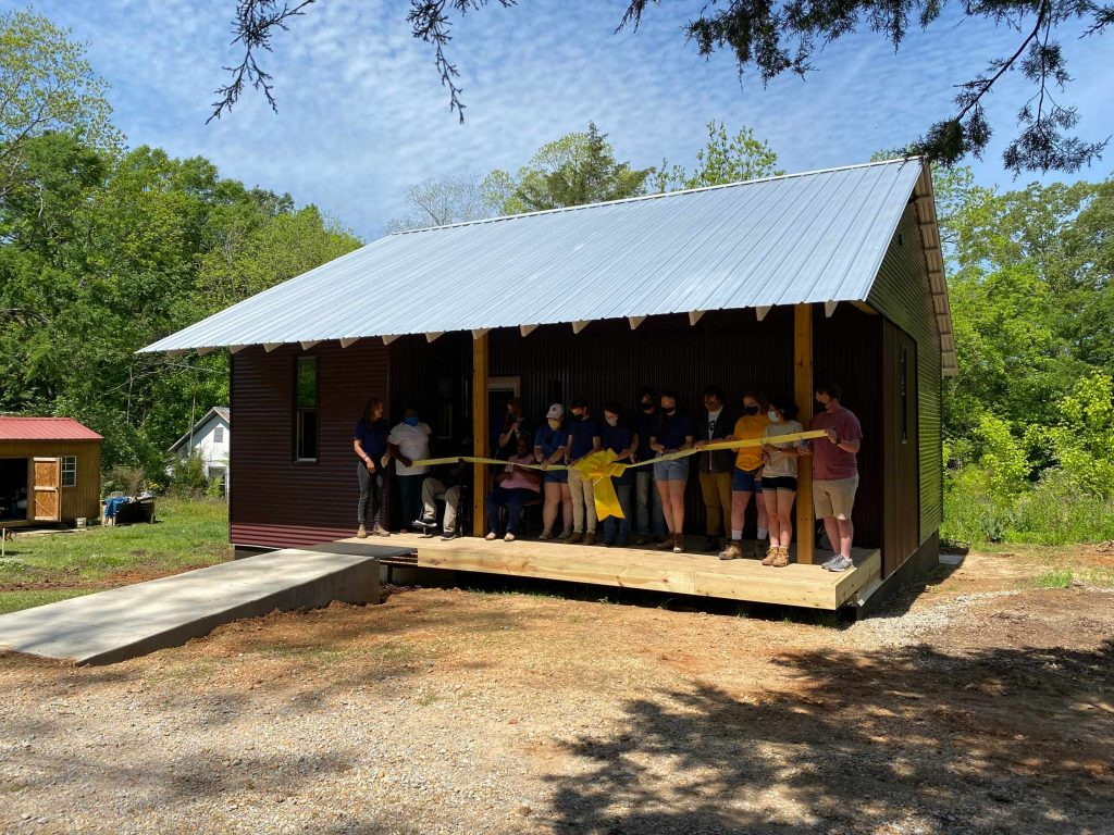 a group of people cut a big yellow ribbon on the porch of a small home