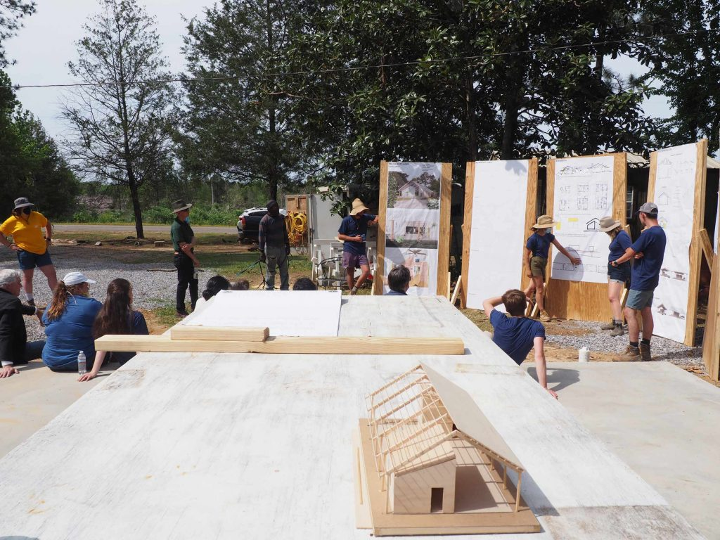 a model of a pole barn is shown in the foreground while a team presents drawings in the background