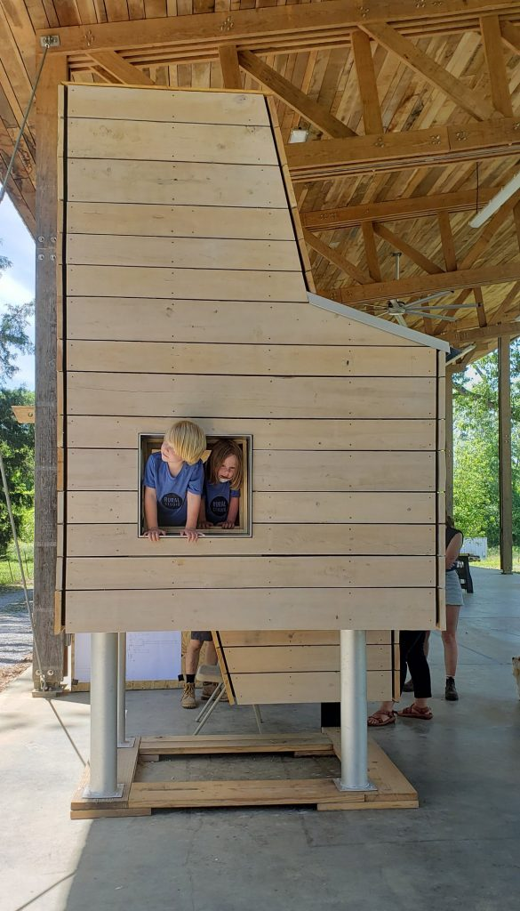 two children play in a small wooden structure