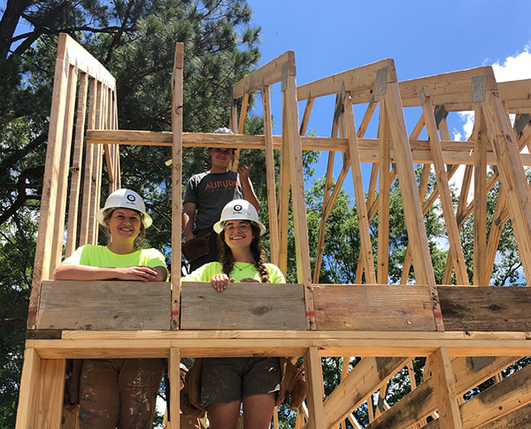 three teammates in truss bays in a newly framed house