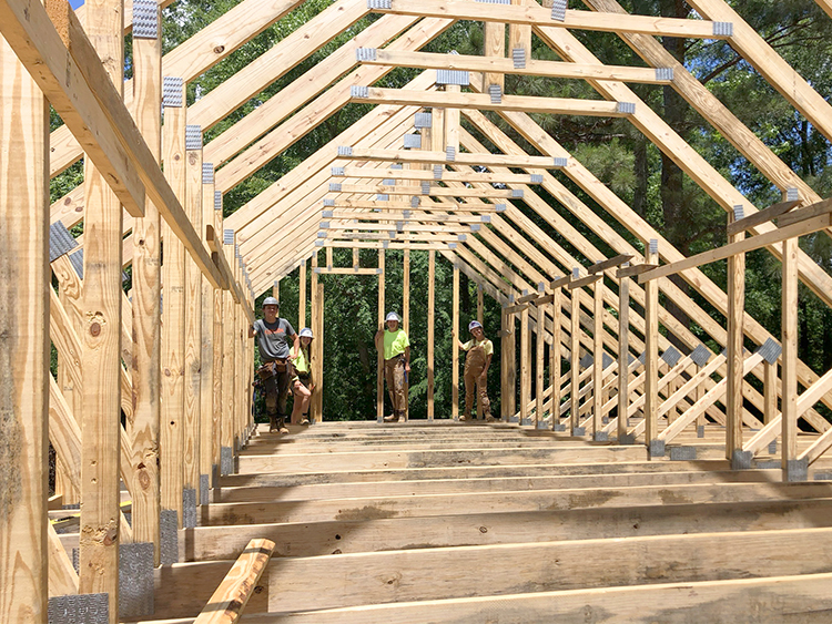 the team that raised trusses posing at the end of the new attic