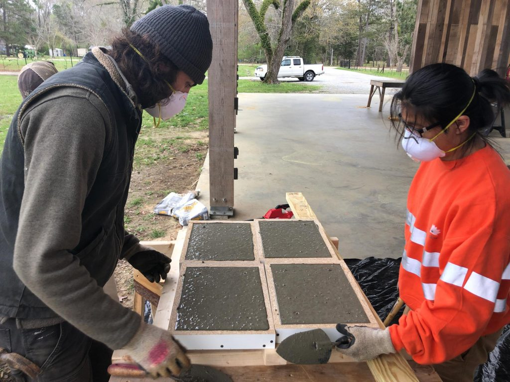 students filling molds with concrete