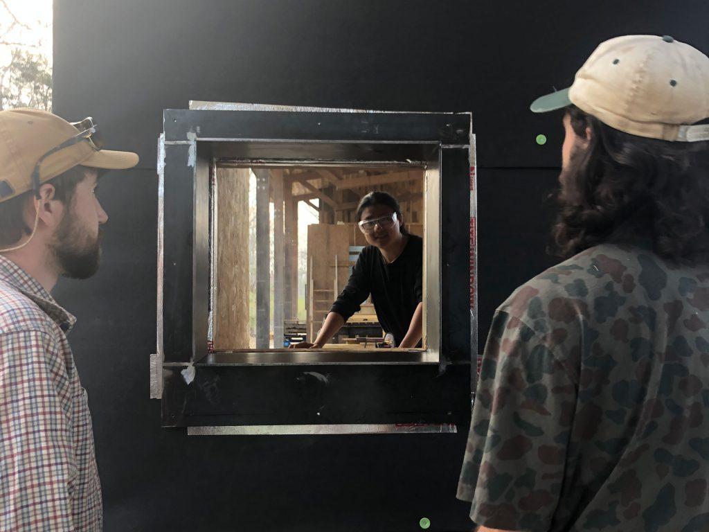 Students looking through mock-up door frame