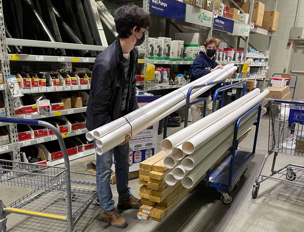 two students load a cart with pvc pipe in a hardware store