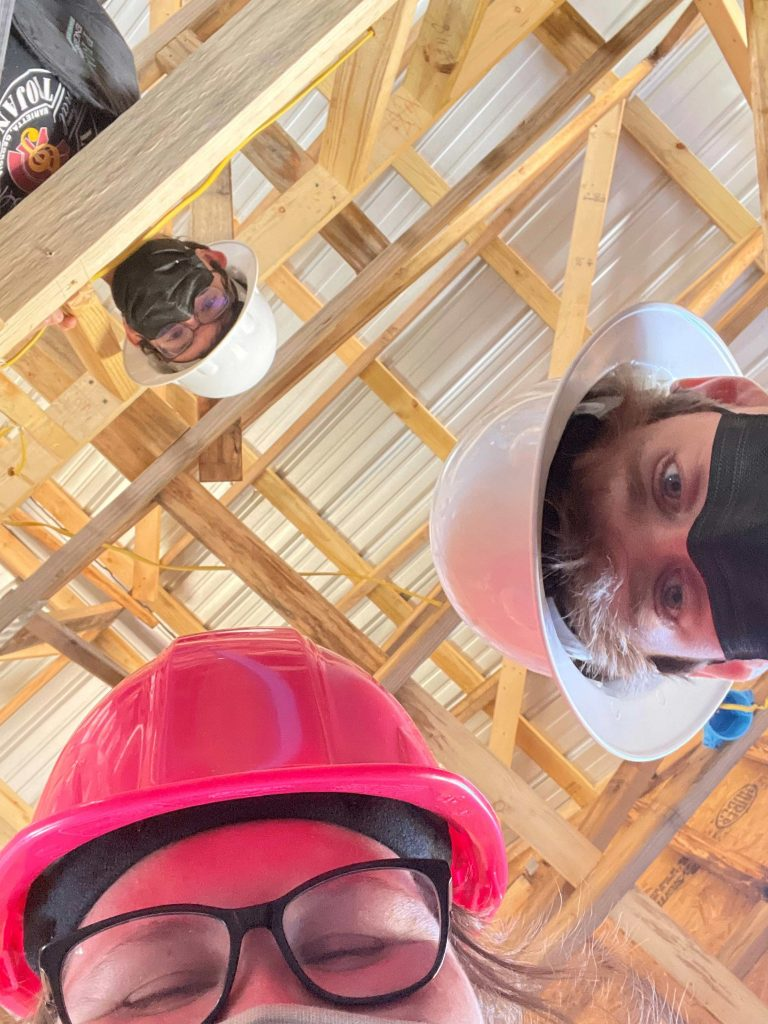 three students wearing hard hats take a selfie from below