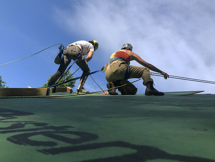 two students maneuvering on a rope system on the home roof