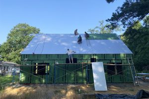 Students screw down a roofing panel on a shady morning