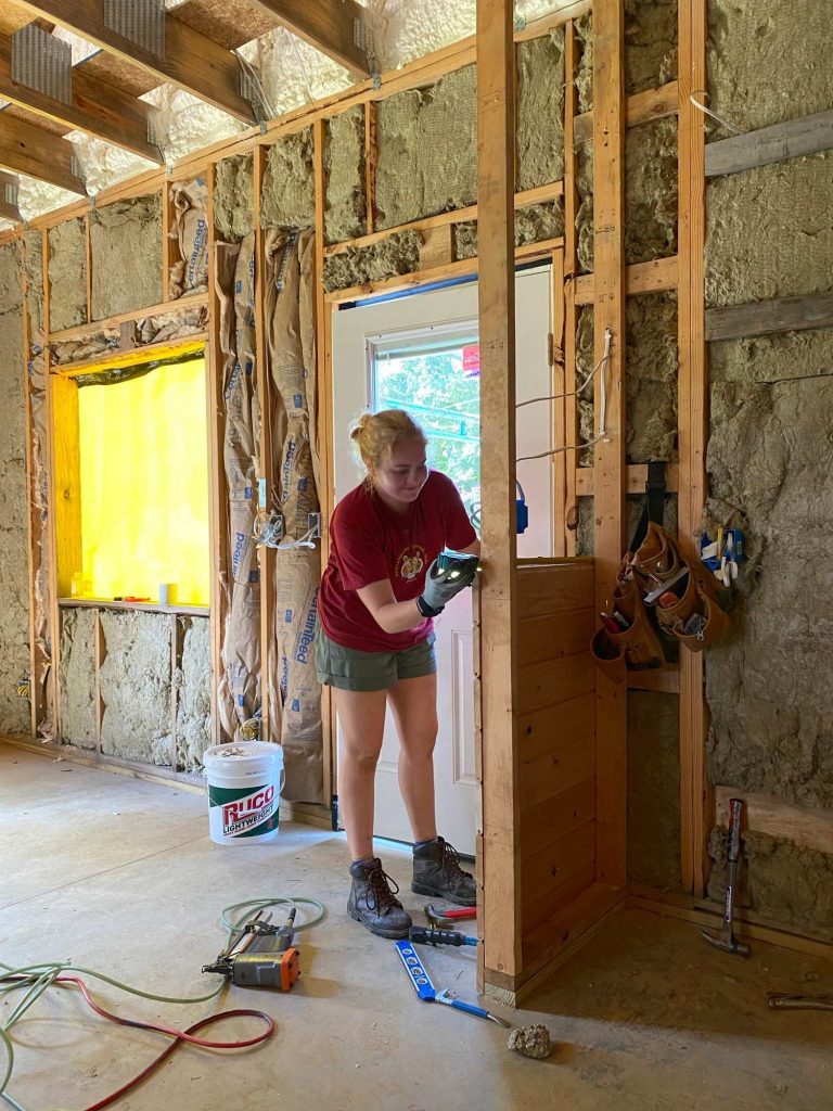 a woman in a red shirt and shorts measures the length between two tall 2x4 studs