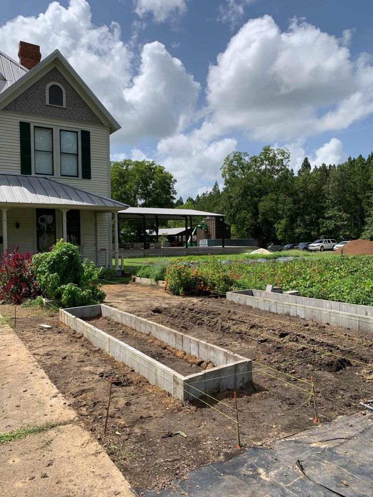 a big plot of dirt with four raised concrete block farm beds and some bright yellow strings framing the beds