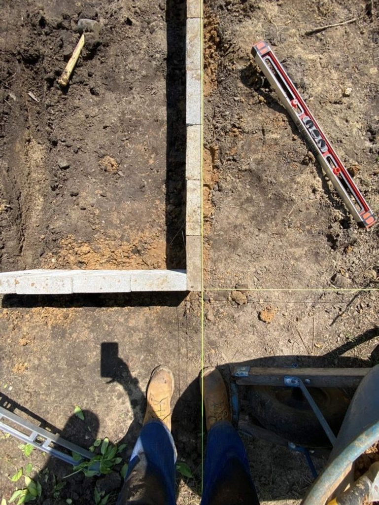 looking down from above, a pair of feet in work boots next to an angle of concrete blocks