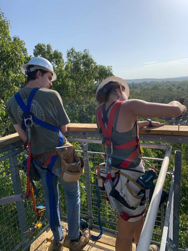 a man and a woman in protective harnesses and hard hats look at a hand railing