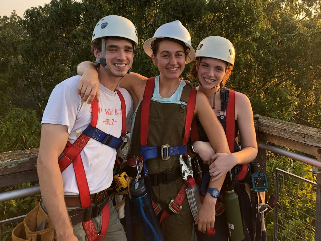 three young people stand together smiling wearing hard hats and harneses