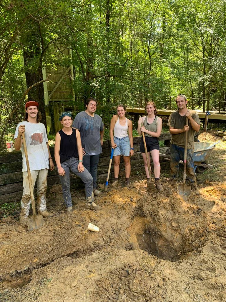 six young people stand in mud holding shovels