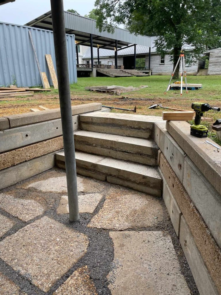 three stairs lead down from a grassy yard into a concrete and gravel outdoor patio
