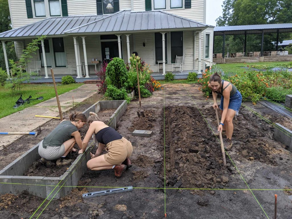 Three female students build concrete block-lined raised beds