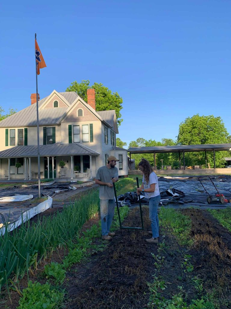 Two students use the broadfork to prepare beds in spring for planting