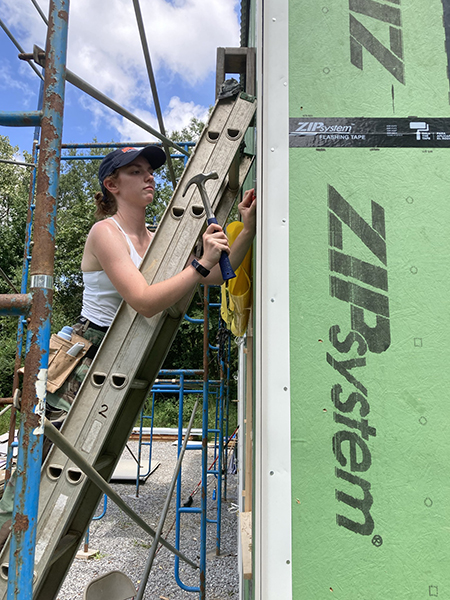 a female student on a ladder applies flashing
