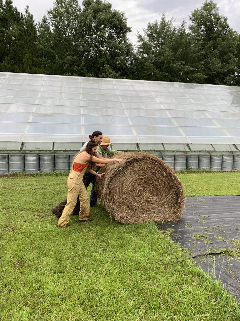 Eric and two student workers push a bale of hay