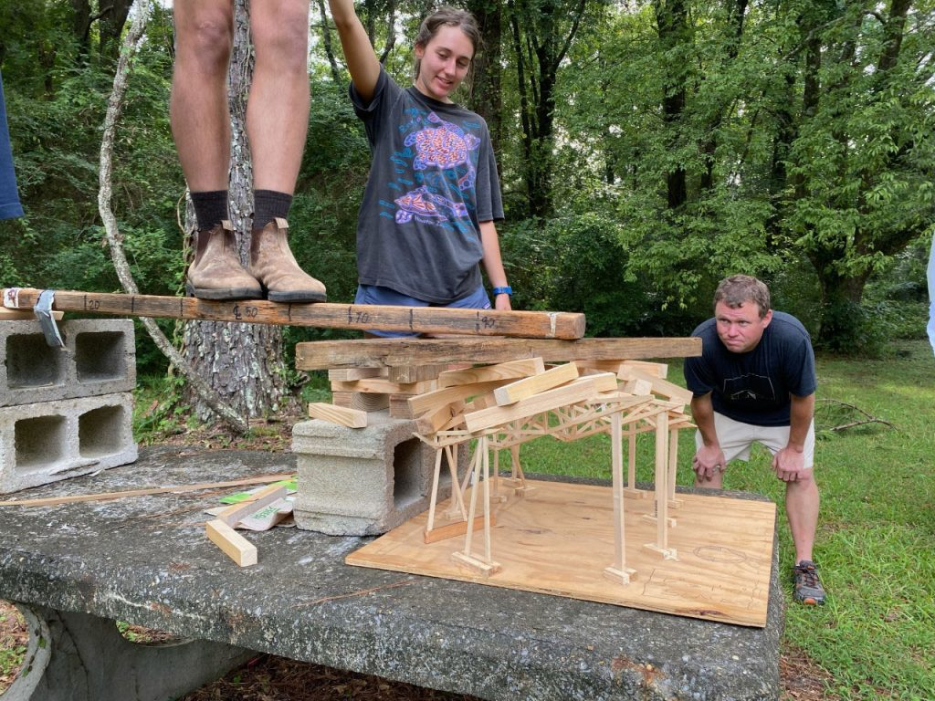 Students standing on a wood model of Moundville Pavilion to test strength