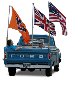 Passengers riding in the back of Director Andrew Freear's vintage baby blue Ford truck. Flags of Auburn University, the United Kingdom, and the USA fly in the back of the truck