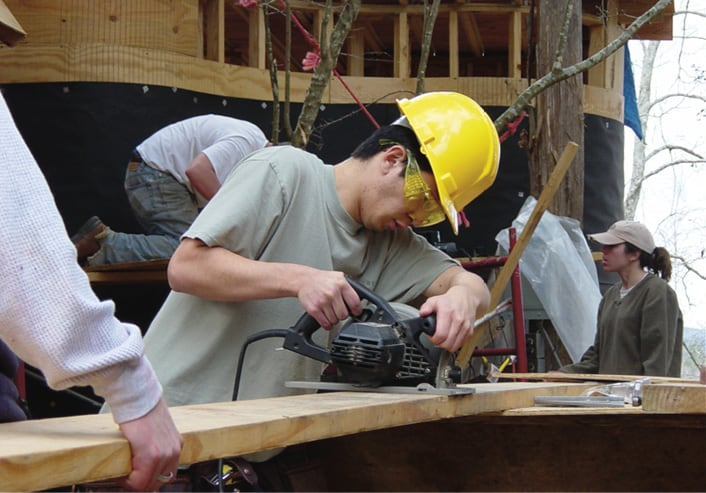 Rural Studio 2003 student sawing a board