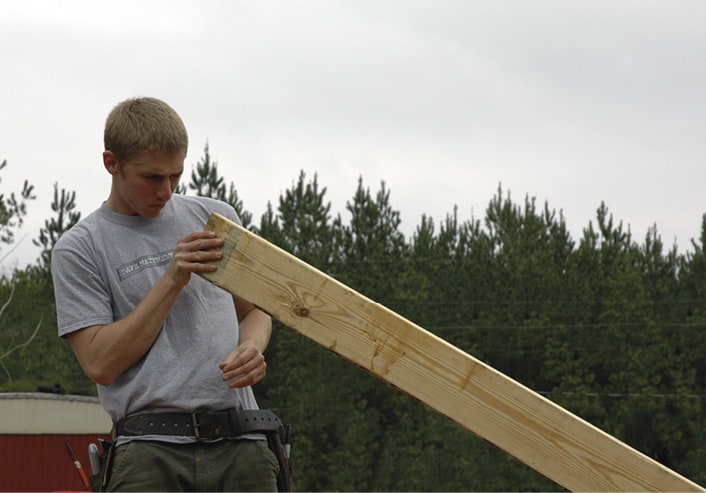 Rural Studio 2005 student lining up a board