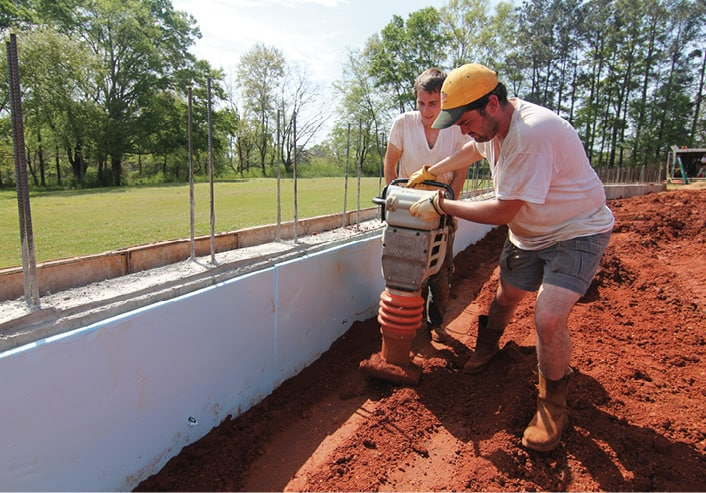 Rural Studio 2012 students smoothing the ground for a foundation