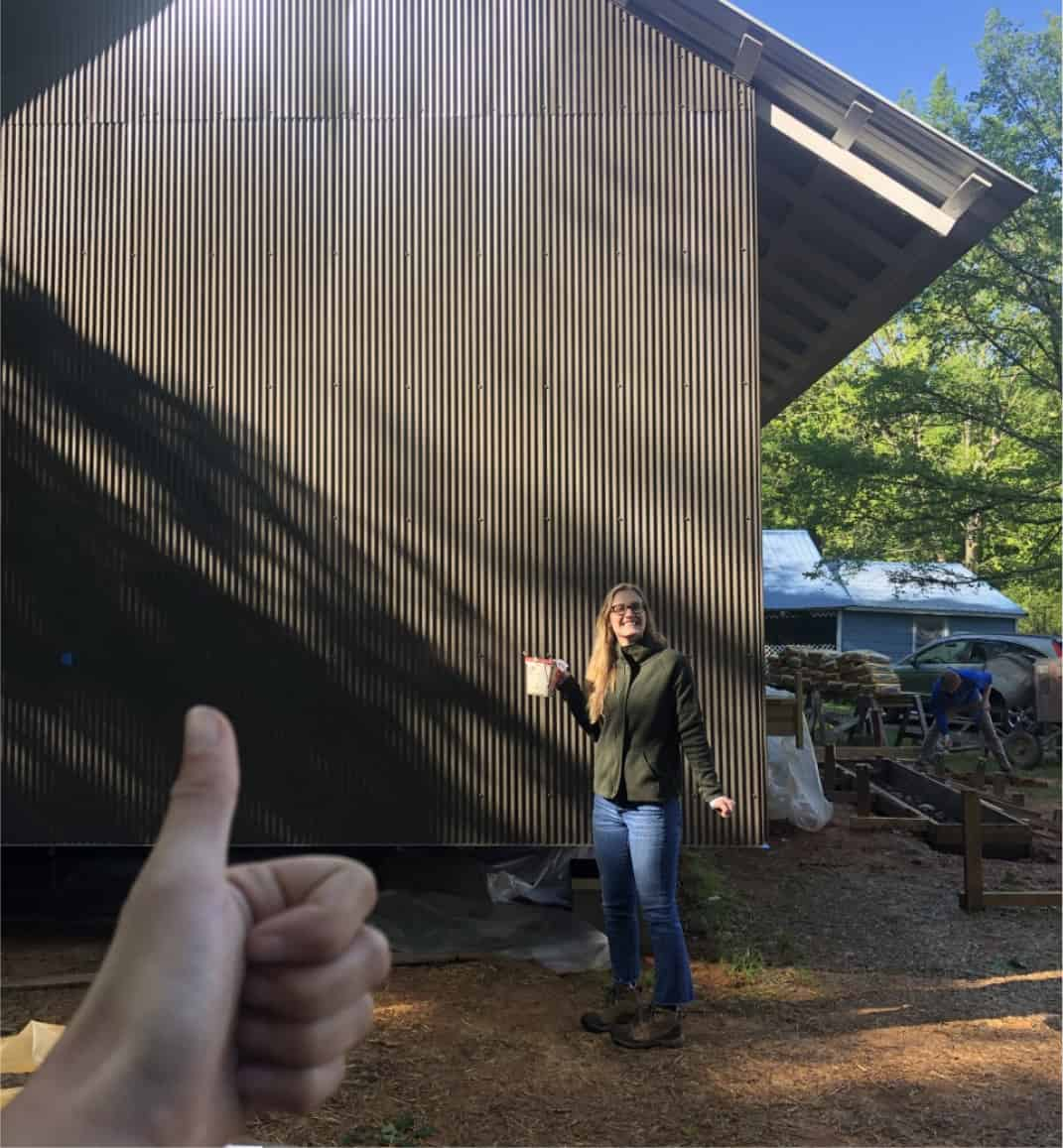 student giving thumbs up in front of house