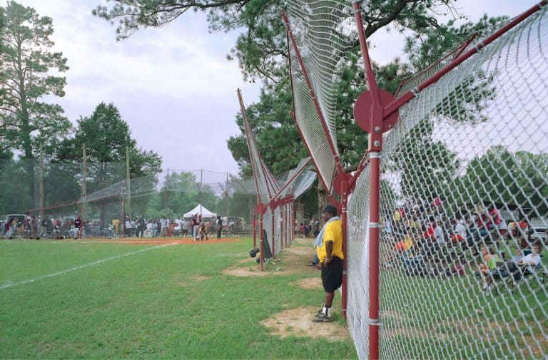 A coach stands outside of the dugout and watches the game