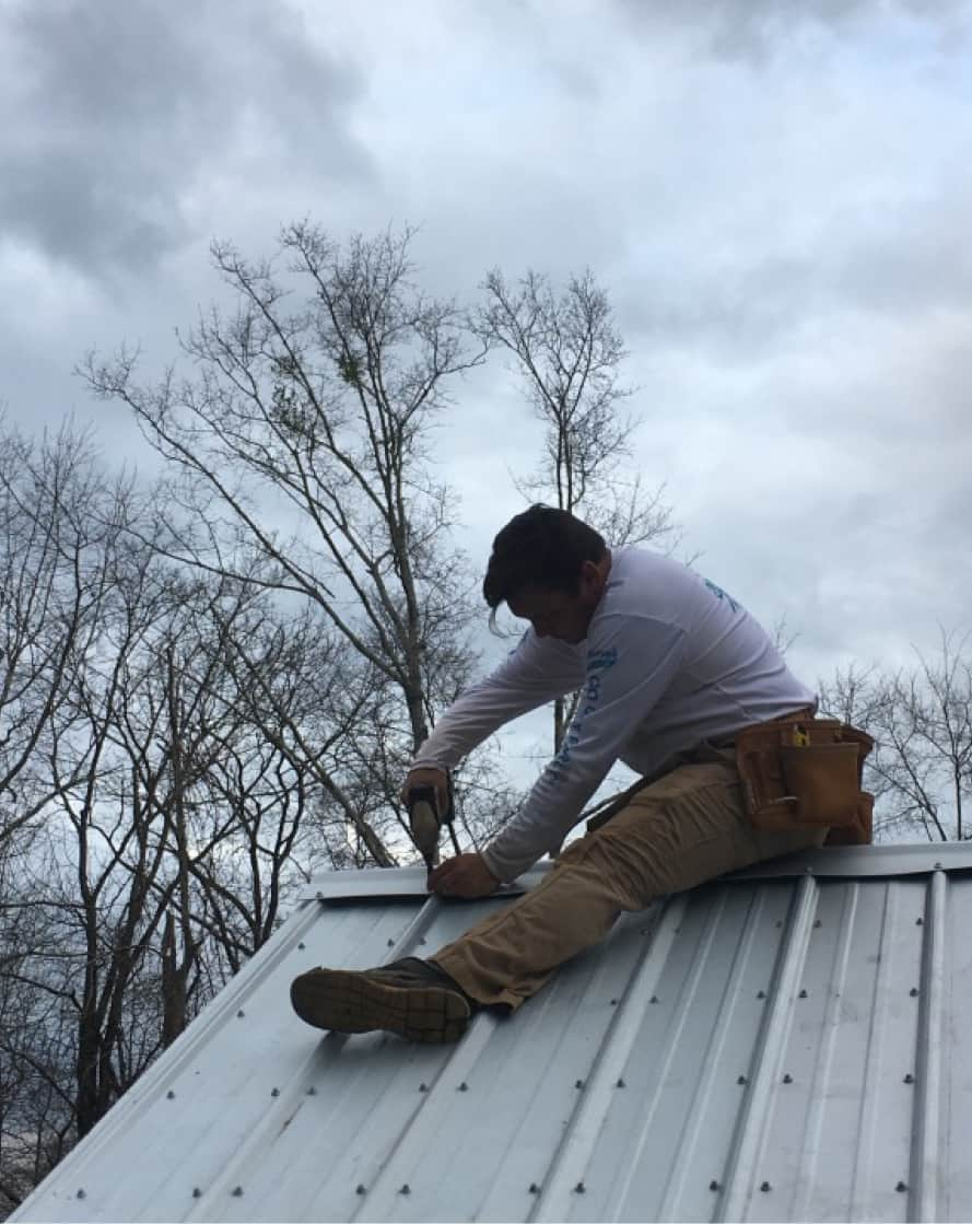 male student working on roof