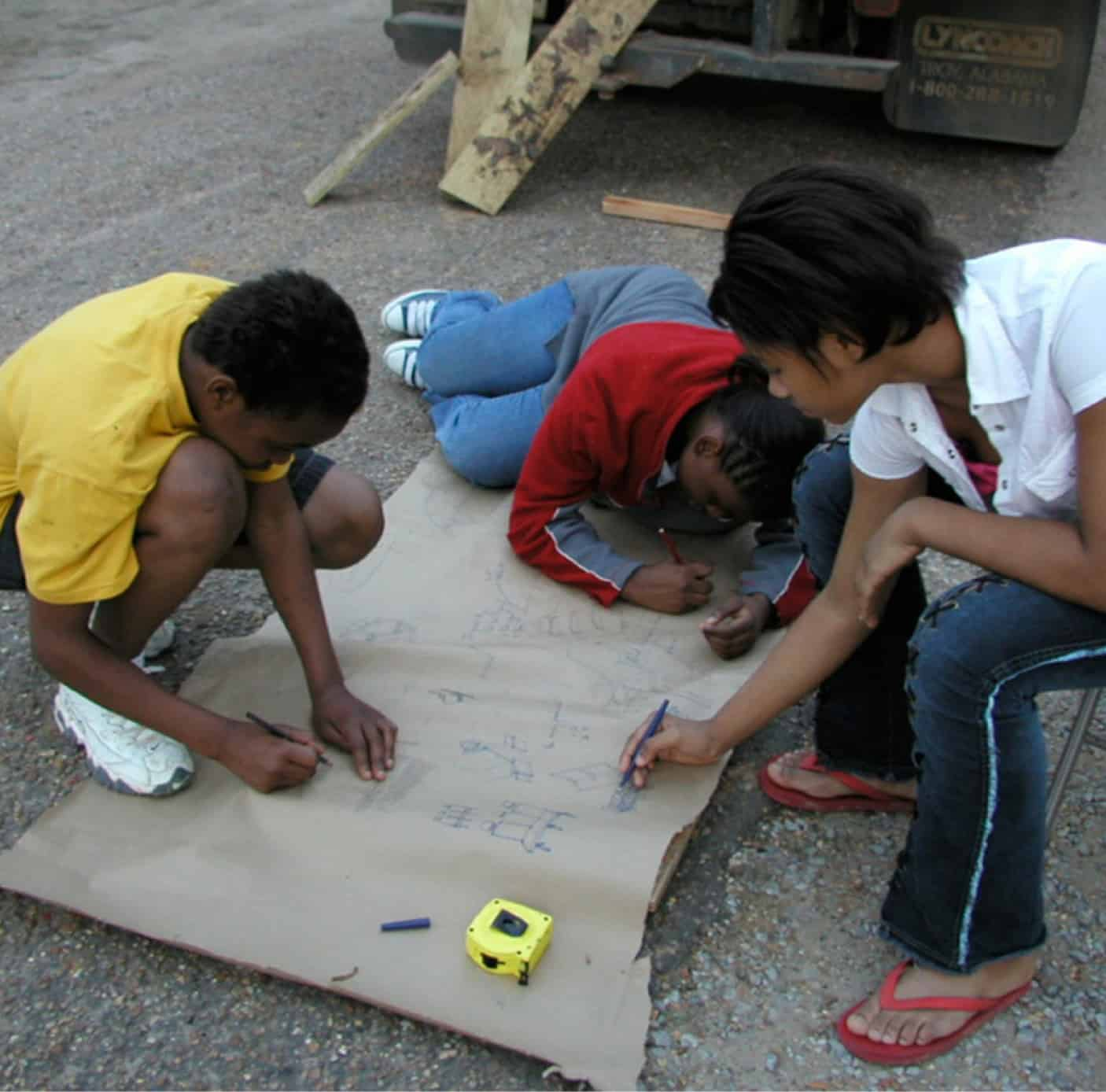 students drawing on kraft paper spread across the ground