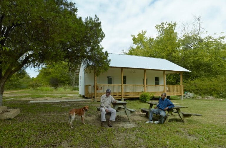 featured image of Turner, man, and dog at picnic tables with house in background