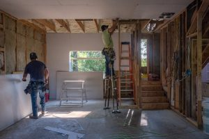 two drywall hangers install a ceiling
