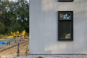 a one-point perspective view of a window and grey corrugated siding